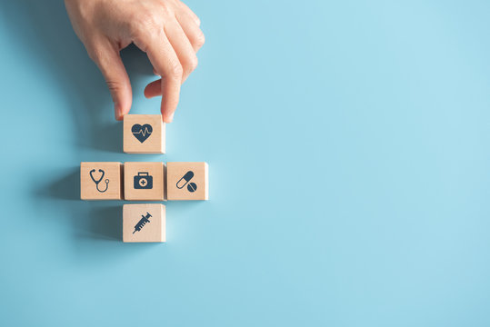 Health Insurance Concept, Hand of woman arranging wood cube stacking with icon healthcare medical on blue background, copy space.