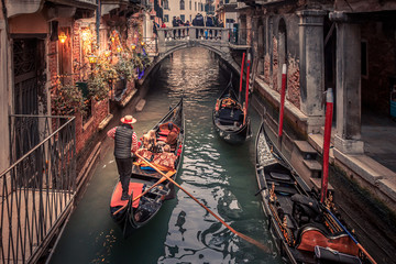 Wall Murals Gondolas Gondolier rowing down a narrow canal in venice with christmas lights illuminating his gondola