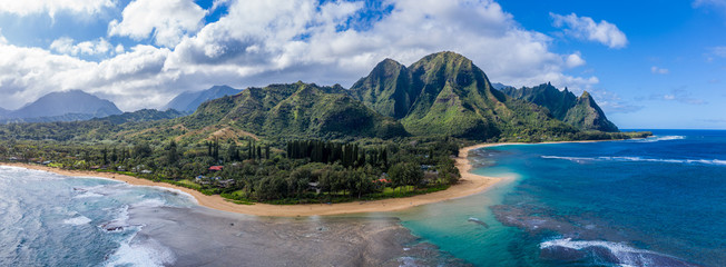Aerial panoramic image off the coast over Tunnels beach on Hawaiian island of Kauai with Na Pali mountains behind Wall mural