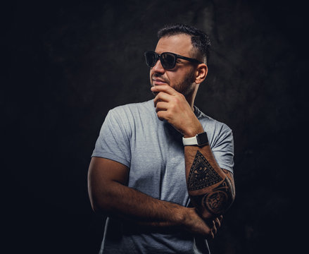 Adult handsome man in a grey shirt and sunglasses, with tattoos on his hand, wearing his watches in a dark studio isolated on grey background, looking cool and thoughtful
