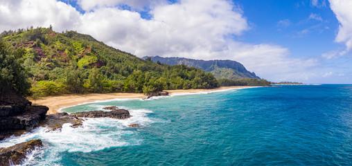 Aerial panoramic image off the coast over Lumaha'i beach on Hawaiian island of Kauai with Na Pali mountains behind