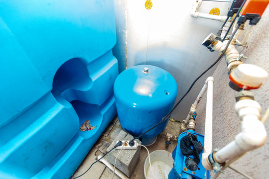 water tanks and pumps for water supply in the basement of the cottage