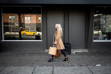 Woman with shopping bags walking along urban sidewalk