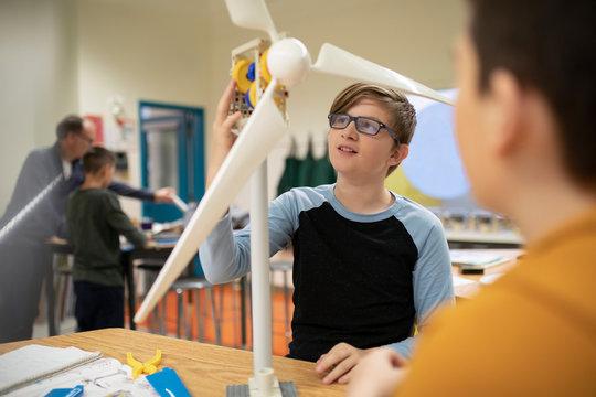 Junior high boy students assembling wind turbines in classroom