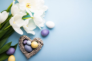 Wall Mural - Naturally colorful dyed Easter eggs on blue background. Happy Easter holiday theme, banner