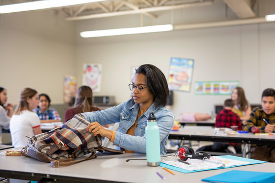 Junior high girl student looking in backpack in classroom