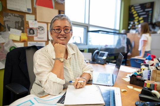 Portrait confident senior female junior high teacher in classroom