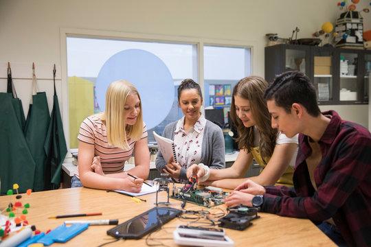 Junior high teacher and students assembling electronics circuit board