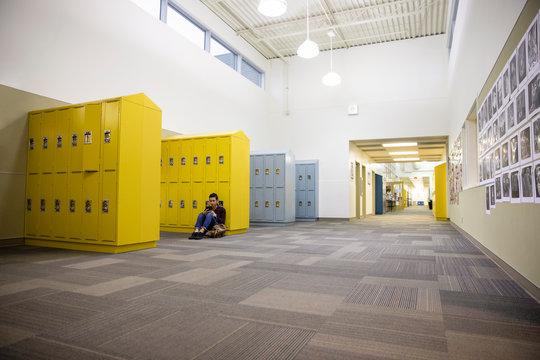 Junior high boy student using smart phone at lockers in empty corridor