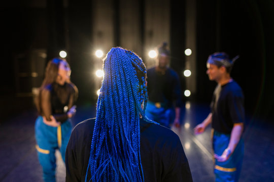 Hip-hop dancer with long braids on stage