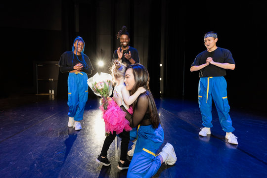 Cute girl ballerina giving flowers to hip-hop dancer on stage