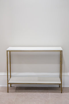 Light colored white and bright empty accent side table with a marble top and gold finishes with nothing on it