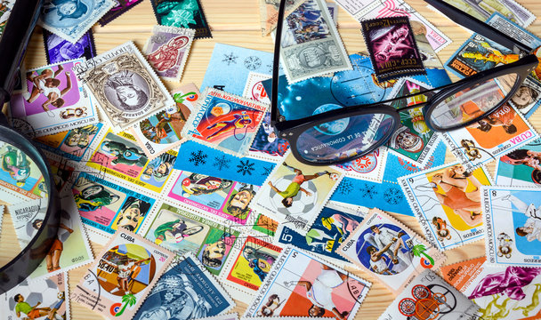 Dolgoprudny, Moscow region, Russia. 02-24-2020. A collection of postage stamps. Glasses, a magnifier and a large number of different postage stamps are on the table