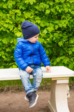 two years child sitting on a stone bench