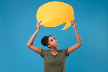 Pretty young african american woman girl in casual t-shirt posing isolated on bright blue background. People lifestyle concept. Mock up copy space. Hold yellow empty blank Say cloud, speech bubble.