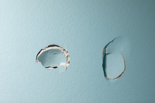 turquoise blue wall in a home with two holes in the sheetrock from a wall being punched by hand