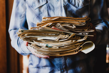 the guy holds a stack of old Newspapers with books, close-up without a face.