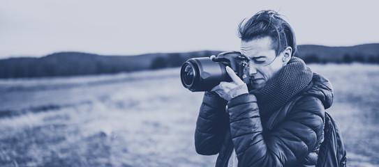Woman photographer takes photos in the mountains