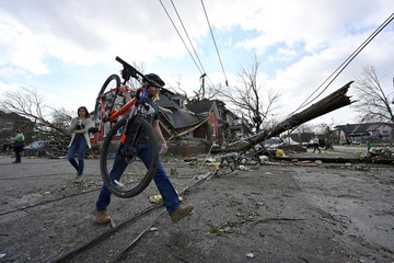 Ben Mongold carries his bike over downed power lines after a tornado hit eastern Nashville