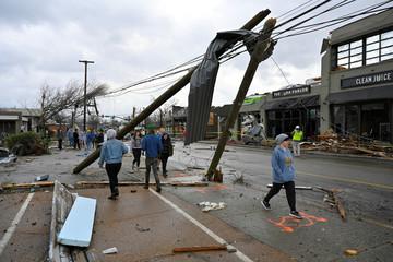 People walk past damaged power lines on Woodland Street after a tornado hit eastern Nashville