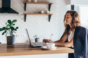 Young woman sitting in front open laptop and working at home