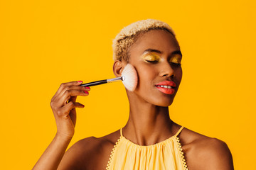 Portrait of a beautiful young woman applying cover up loose powder  to her cheeks with a makeup brush, eyes closed