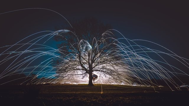 Steel wool spinning above the ground near a tree during the night