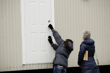 King County property agent Tami Elmer closes the door to one of 18 modular units that King County is using to house patients for treatment and isolation in relation to coronavirus in Seattle