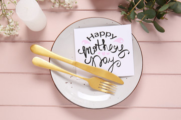 Table setting with card for Mother's day dinner on white  wooden background