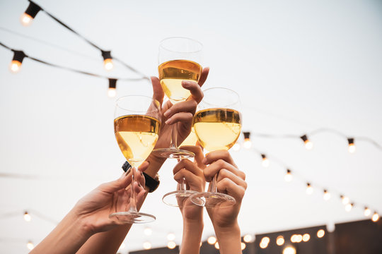 Group of people in party and celebrating together with white wine. Happy Asian people enjoy partying in festival and celebrate with white wine on the roof top bar and restaurant of 5 stars hotel.
