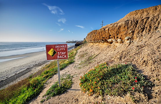 Sign warns that the cliffs behind Pacific Beach, California are not stable