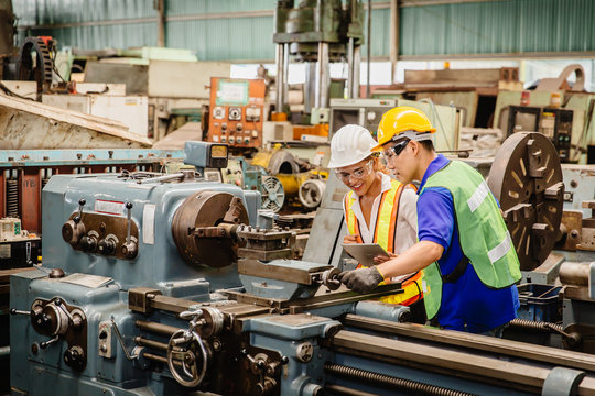 Mix race worker working together help each other to work in heavy industry machine wearing safty suit in factory production line.engineer coworking with staff.