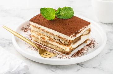 Fototapeta Traditional italian dessert tiramisu on a white plate on a marble table. Close-up. Selective focus obraz