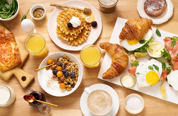 Top view image of brunch menu on wooden table. Healthy sunday breakfast with croissants, waffles, granola and sandwiches. Flatlay with tasty food