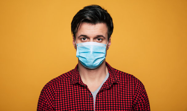 Young serious man in a protective medical mask looks on camera. Man wearing face mask because of Air pollution or virus epidemic.
