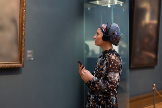 A woman in a museum listens to an audio guide
