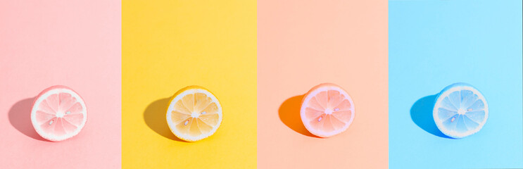 Banner format. Sliced lemon in different colors. Summer, freshness concept. Yellow, pink and blue lemons. Citrus pop-art background. Minimal fruit concept.