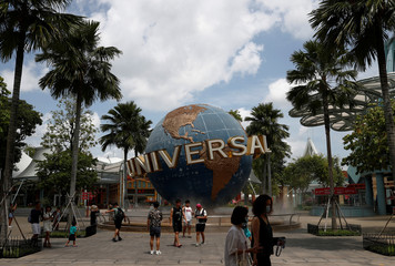 People pose for photos, as tourism takes a decline following the coronavirus outbreak, at Universal Studios Singapore in Sentosa