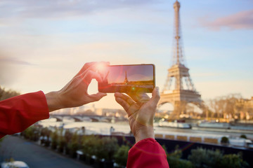 Close up of  man hand taking a photo of the sunset in Eiffel tower, Paris. France