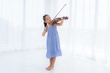 Asian Girl are playing violin in the white room.