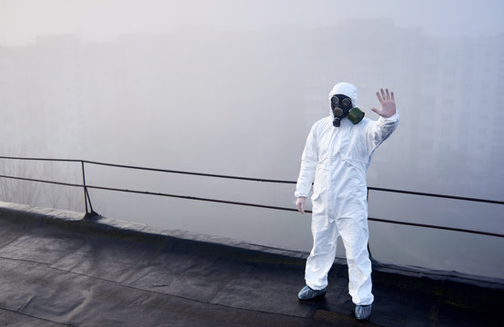 Human in protective clothing and gas mask, showing stop sign, standing on the roof of high building, making research on environmental air pollution