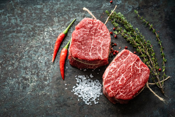 Photo sur Plexiglas Steakhouse Two juicy filet Mignon beef steaks prepared for grilling with spices and herbs, top view and copy space