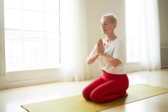 Yoga, meditation, vitality, relaxation and health. Indoor image of healthy peaceful mature female sitting on her heels, keeping eyes closed and hands pressed together in front of her, meditating