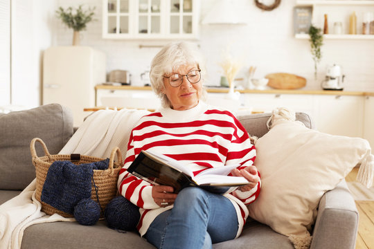 Portrait of stylish attractive female pensioner in round eyeglasses relaxing at home with good book. Joyful elderly woman wearing spectacles, reading bestseller, sitting comfortably on sofa