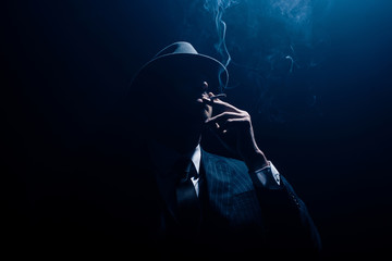 Silhouette of mafioso in suit and felt hat smoking cigarette on dark blue background Wall mural