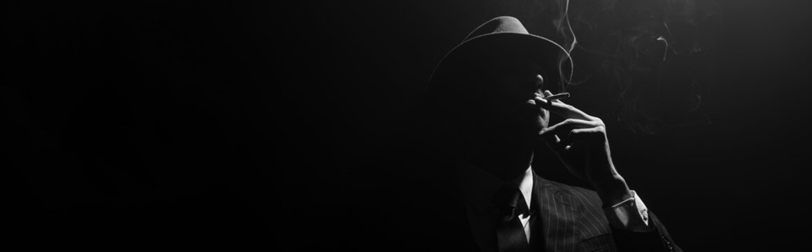 Monochrome image of mafioso silhouette smoking on black background, panoramic shot
