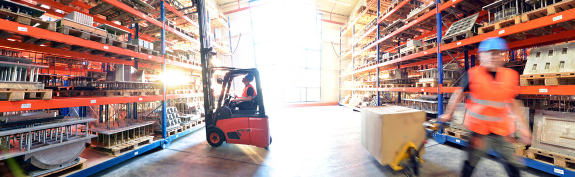 logistics and transport workers in a goods warehouse with goods for storage and shipping