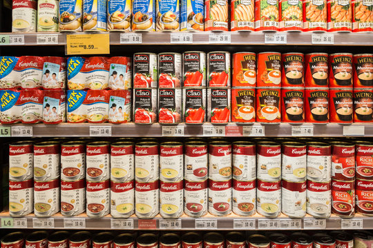 Canned soups are displayed in a supermarket shelf