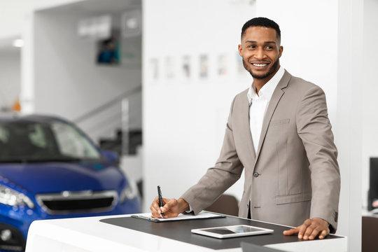 Car Seller Man Standing At Work Desk In Dealership Office
