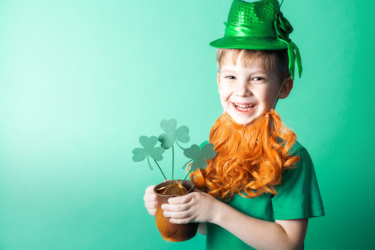 St. Patrick's Day: A little boy in a hat holds a small clay pot with gold coins.